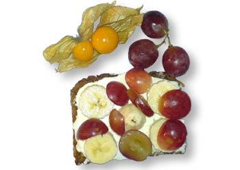 Vollkornbrot mit Frischkäse und Bananen sowie Trauben