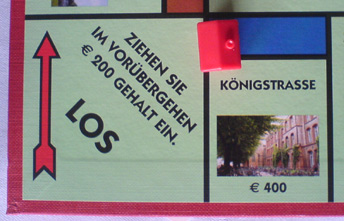 Spielplan der Lübecker Monopoly-Ausgabe. Die teuerste Adresse ist die Königstraße, dargestellt mit einem Foto des Katharineums.