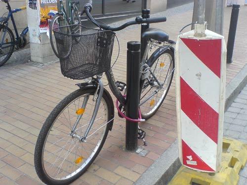 Noch ein Fahrrad, an einem halbhohen Pfosten angeschlossen