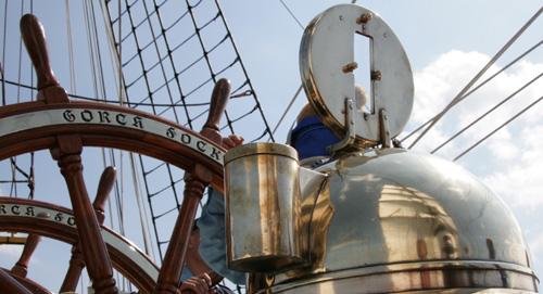 Die Segel der Gorch Fock spiegeln sich im Messinggehäuse nautischer Geräte