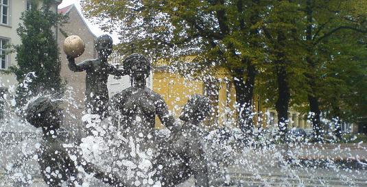 Detailaufnahme vom Brunnen der Lebensfreude: Figuren hinter Wasserstrahlen und Tropfen