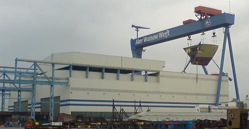Anblick der Werfthalle Warnemünde - am Kran hängt das Segemnt einer neuen Fähre