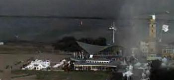 Screenshot des Videos von Webcam des Neptun-Hotels in Rostock-Warnemünde. Das Foto zeigt die Staubwolke des Tornados - und der weiße Fleck am rechten Bildrand scheint eines der Zelte zu sein, die kurz zuvor noch auf der Promenade standen.