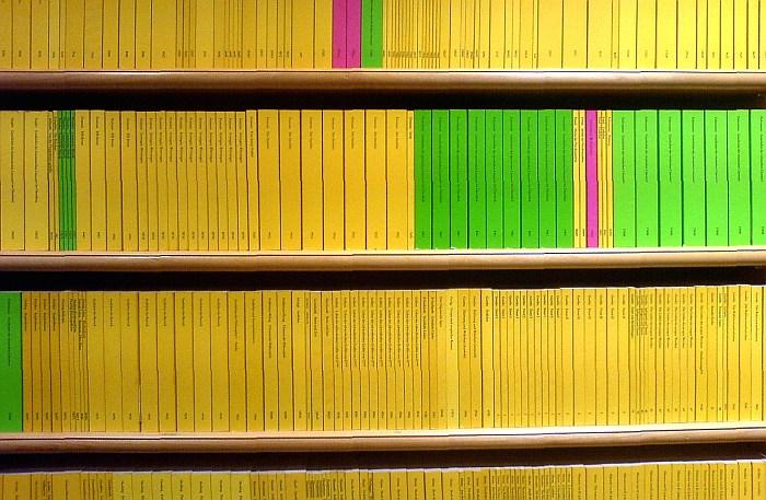 Mehrere Regalmeter mit gelben, grünen und rotenm Reclamheften