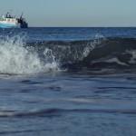 Kleine Welle bricht am Strand