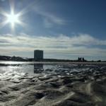 Sonne spiegelt sich in Wasserlache am Strand