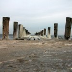Vereistes Spirtzwasser an alten Holzpfählen