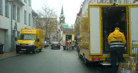 Drei Lieferwagen von Deutscher Post und DHL