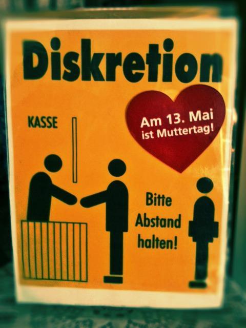 """Schild: """"Abstand halten"""" mit Muttertags-Werbung"""