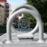 Blick durch zwei Haken an Recyclingcontainern