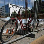 rotes altes Fahrrad am Bauzaun