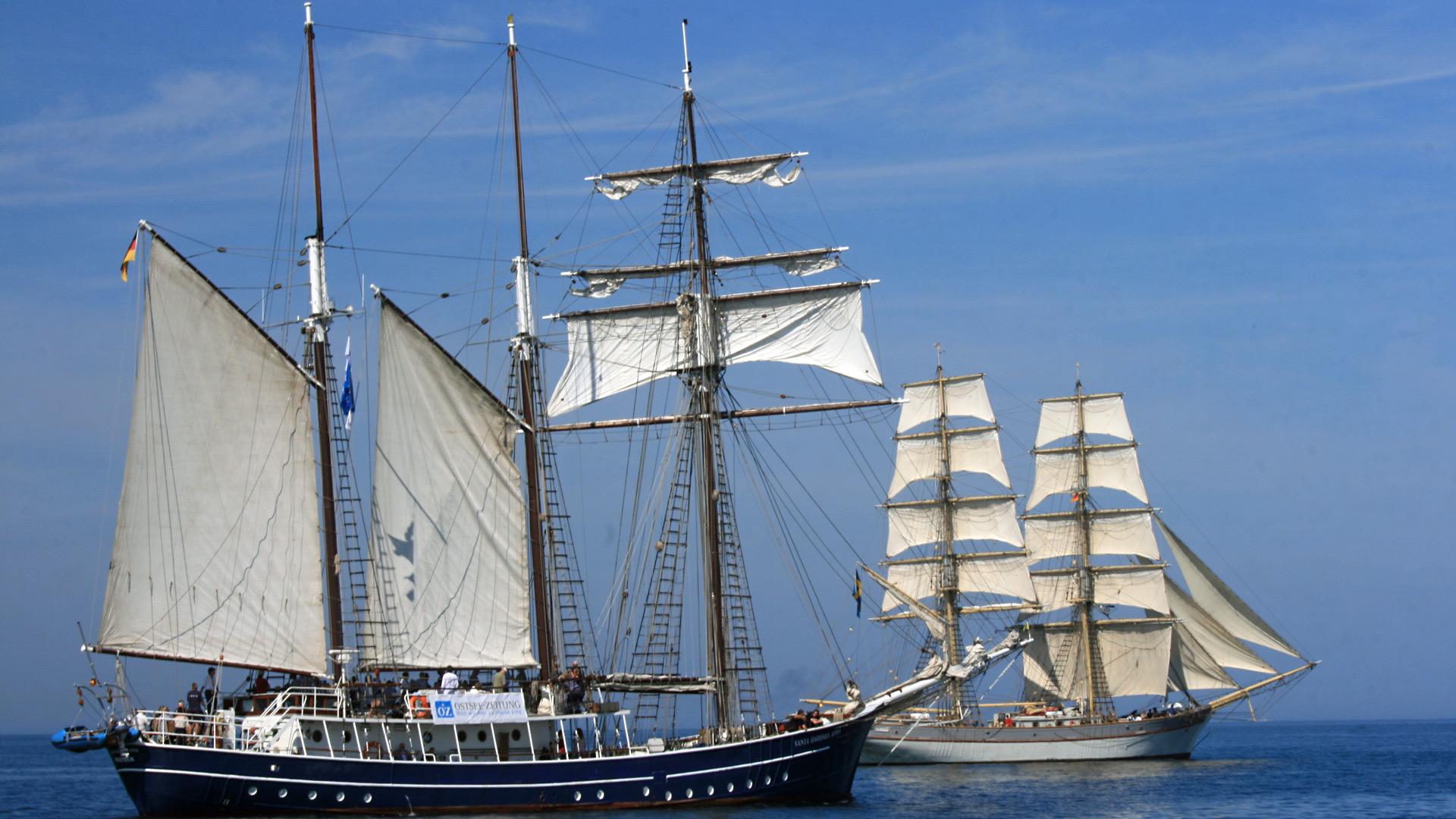 Ein Segelschiff mit blauem Rumpf und ein Segelschiff mit weißem Rumpf, jeweils unter Segeln.
