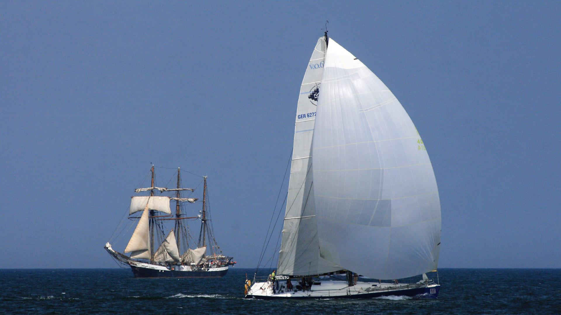 Regatta-Segelboot kreuzt vor Dreimast-Segler.