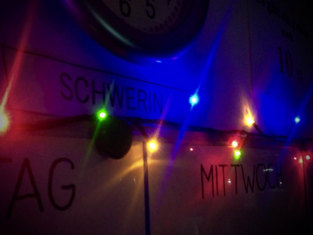 Rote, gelbe, blaue und grüne Lampen eine Lichterkette leuchten über einem Whiteboard.