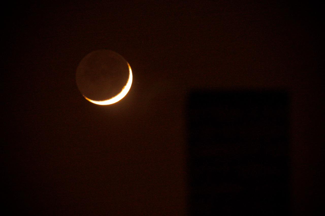 Dünne Mondsichel am rötlich schimmernden Nachthimmel.