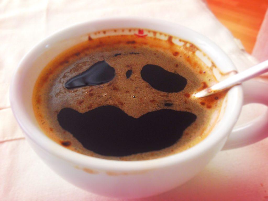 Kaffee in einer Tasse. Drei Löcher in der Crema sehen aus wie ein Gesicht mit zwei traurigen Augen
