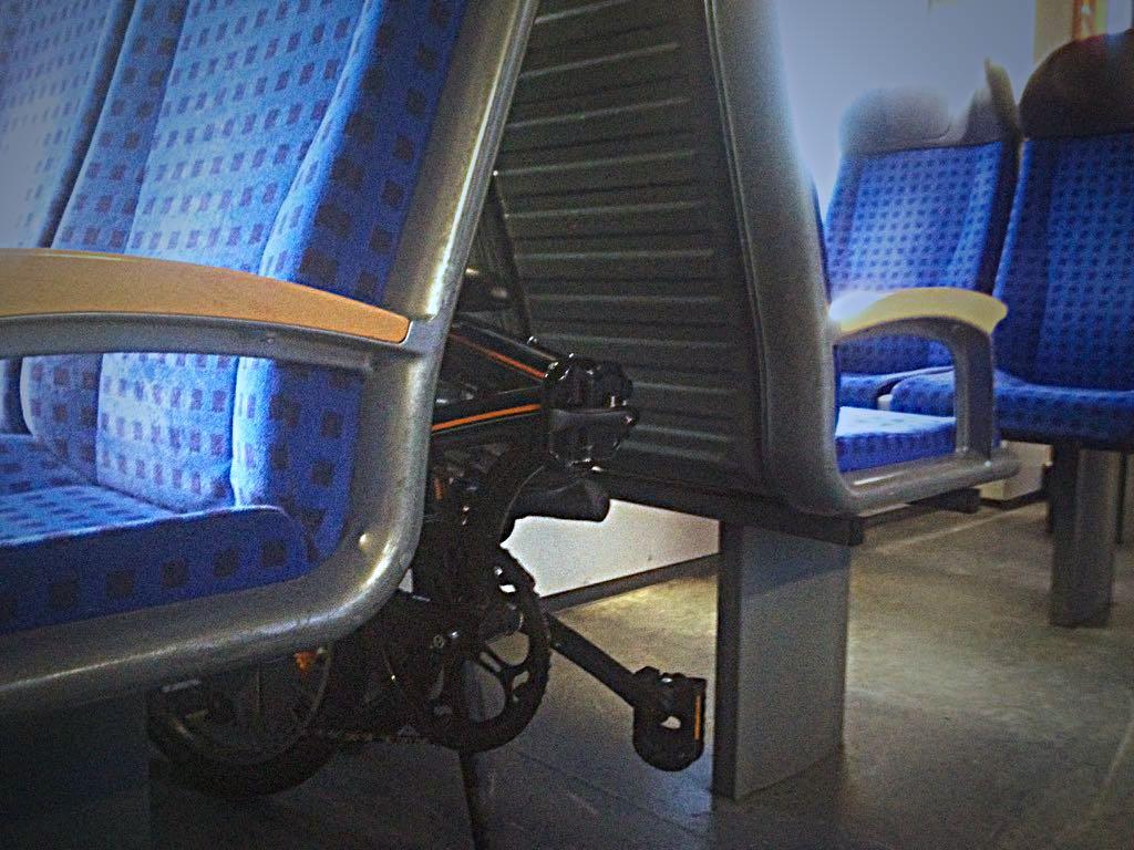 Faltrad zwischen zwei Sitzreihen im Zug.