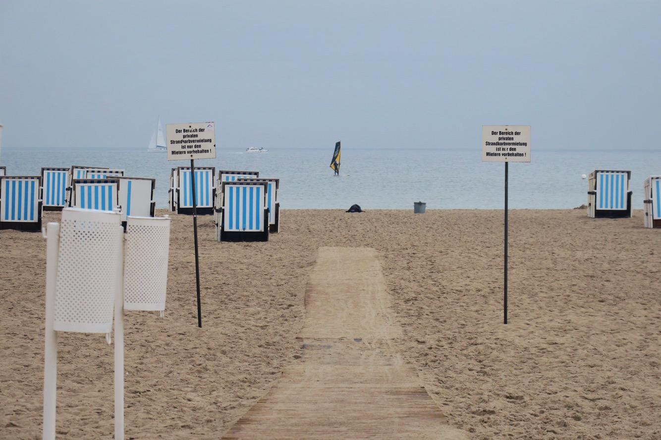 Strand, leere Strandkörbe, ein Surfer auf ruhigem Wasser.