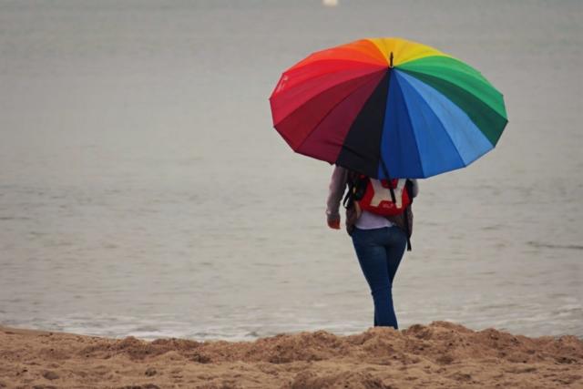 Frau mit buntem Regenschirm beim Strandspziergang.