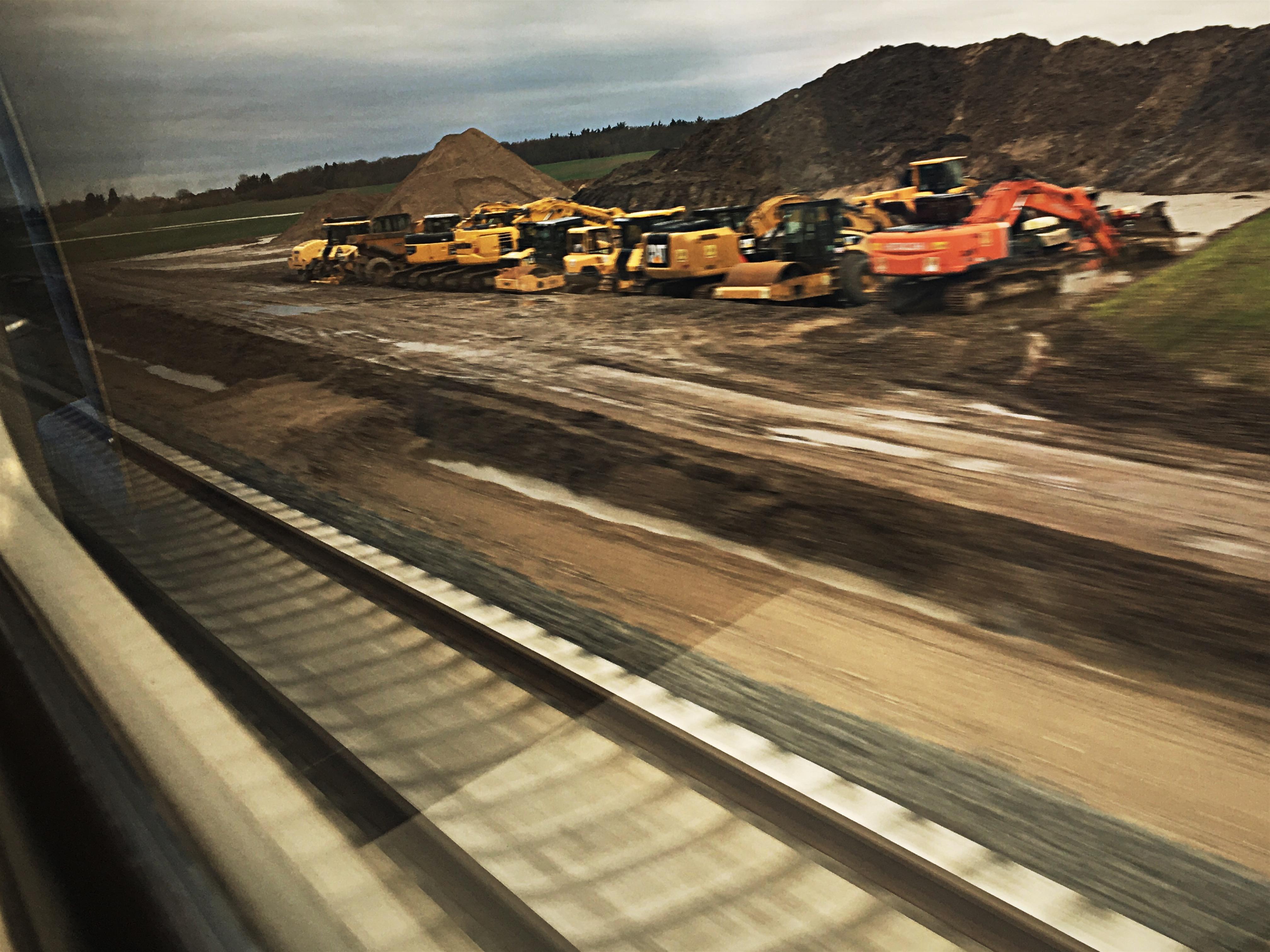 Gelbe und orangene Baufahrzeuge stehen neben einem neu verlegten Eisenbahngleis.