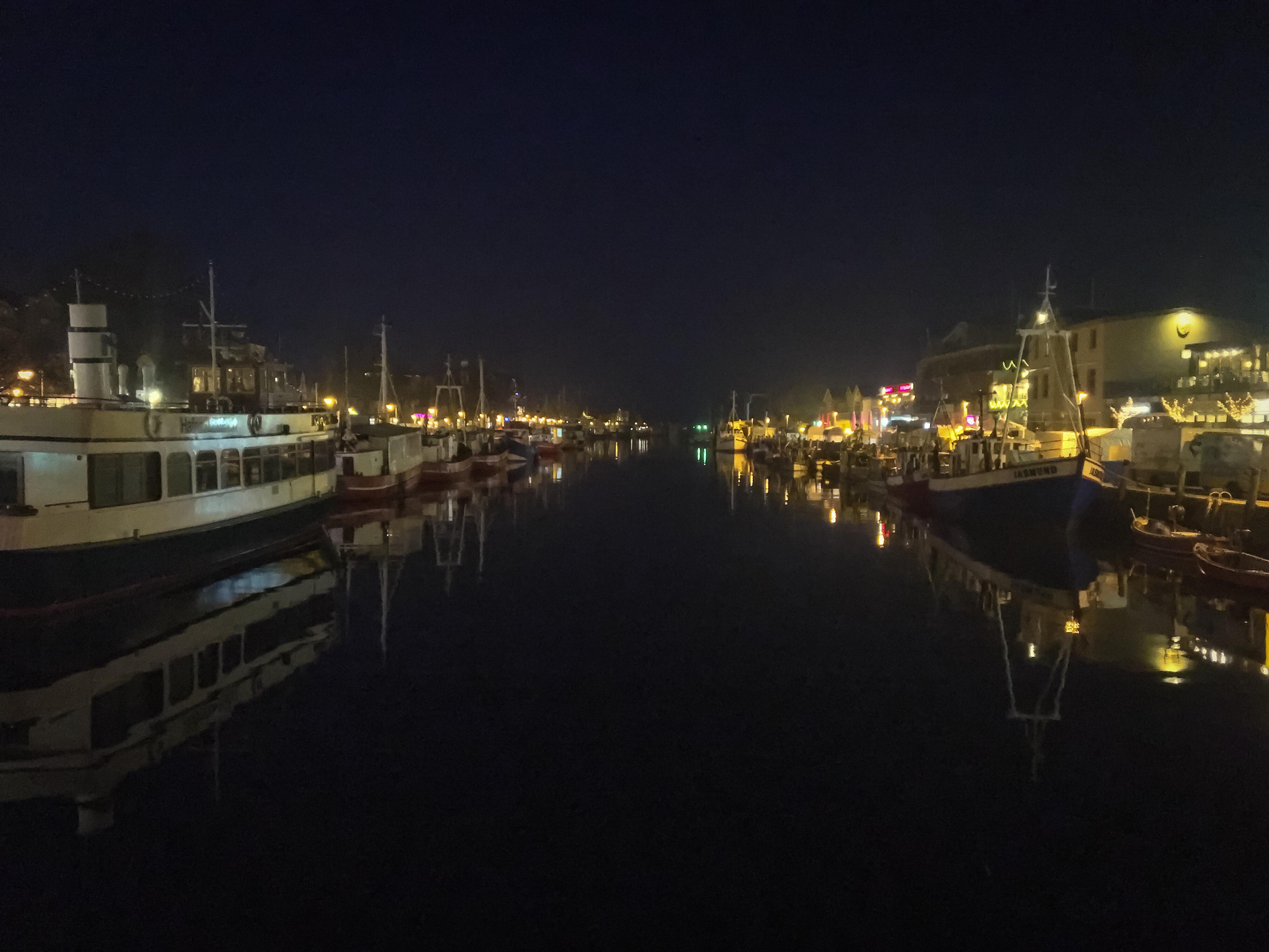 Alter Strom Warnemünde bei Dunkelheit. Schiffe und Leuchtreklamen spiegeln sich im glatten Wasser.