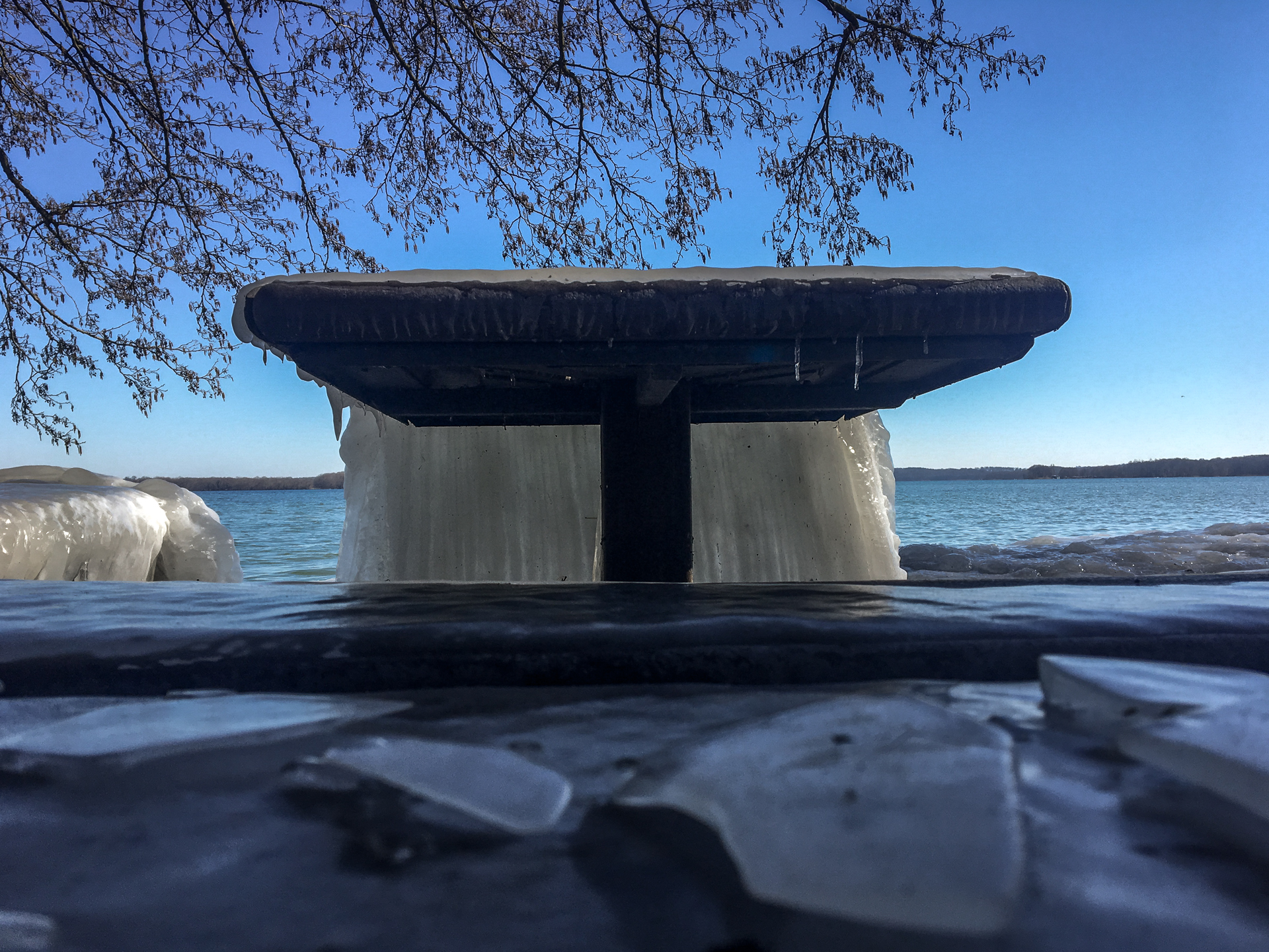 Eine Eiswand hängt von einem Pciknicktisch herunter.