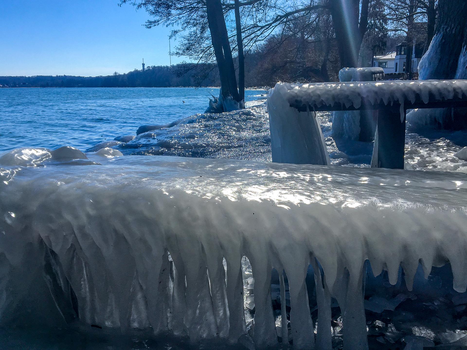 Eiszapfen an einer Sitzbank.
