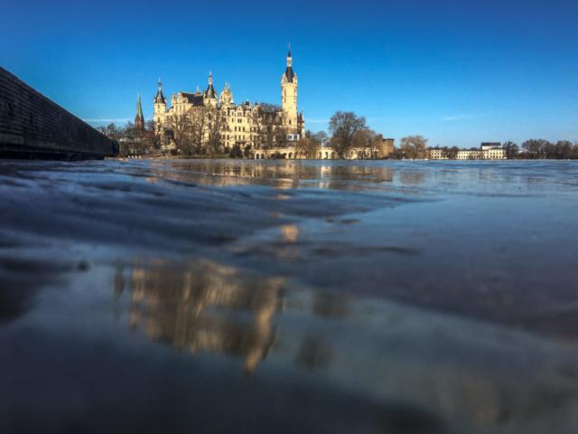 Das Schweriner Schloss spiegelt sich im dicken Eis auf der Schlossbucht.