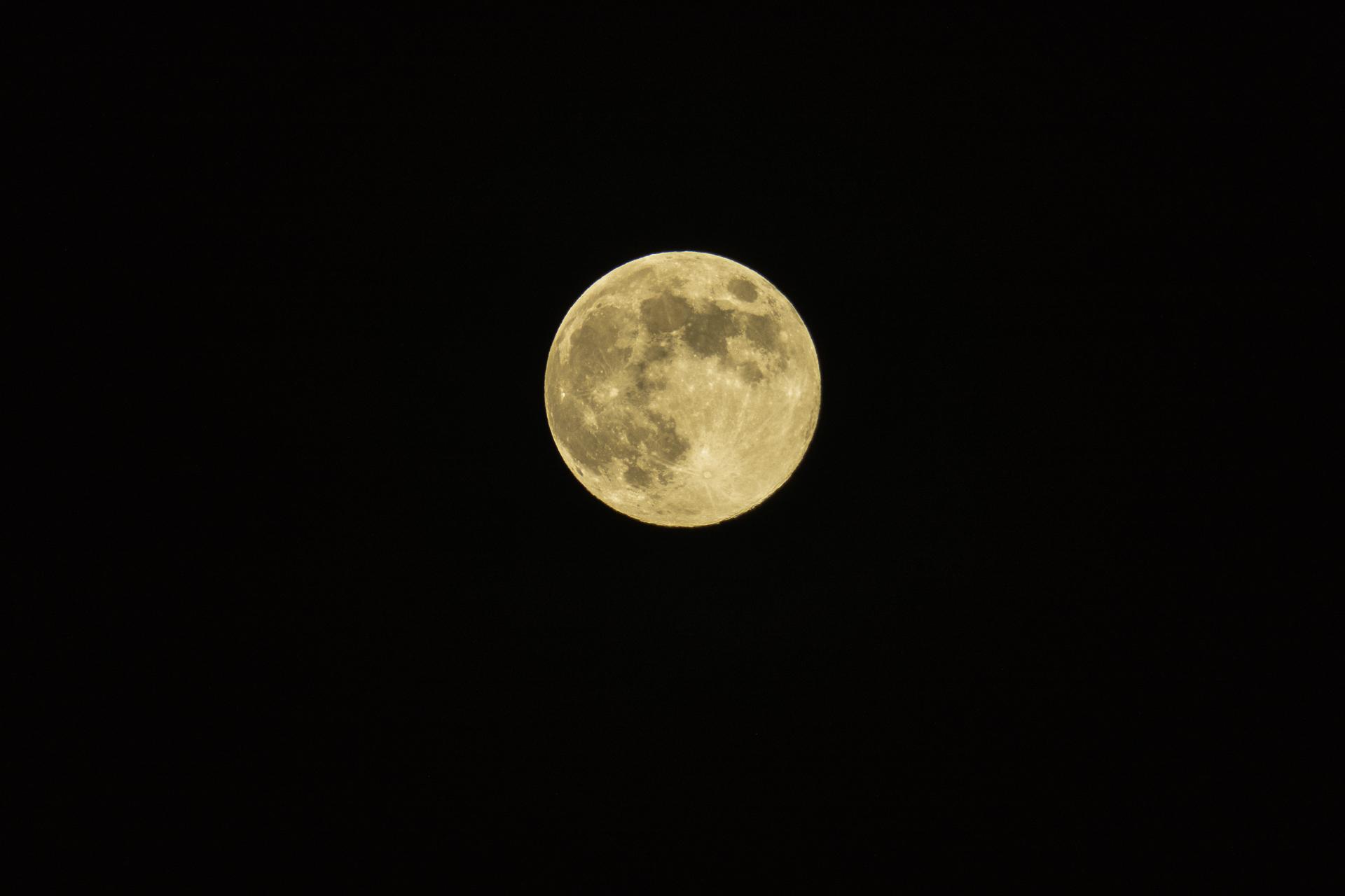 gelb-grau schimmernder Vollmond mit dunkelgrauen Kratern