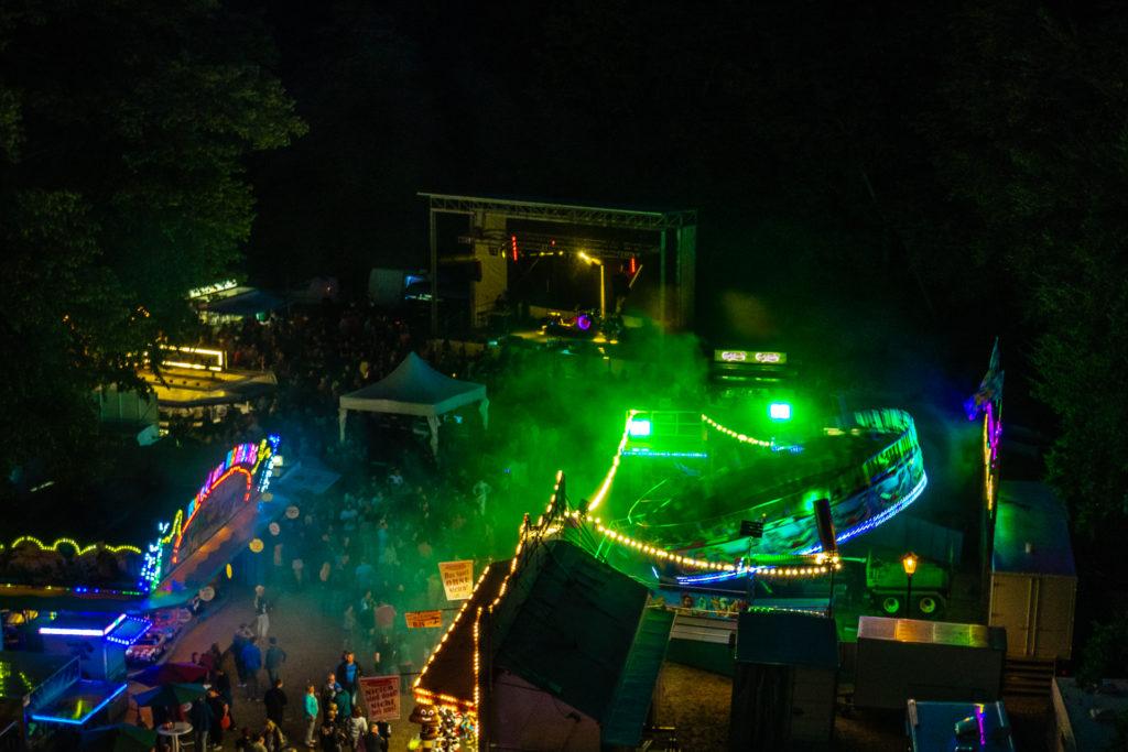 Blick aus einem Riesenratt auf einen bunt leuchtenden Rummel abends