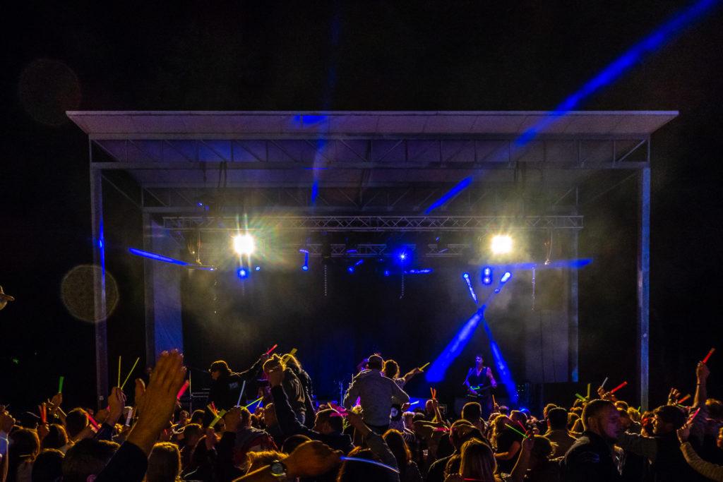 Eine Musikbühne nachts, mit blauen Scheinwerferstrahlen