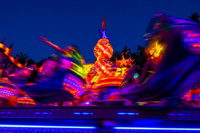 Langzeitbelichtung: Karussell-Gondeln ziehen bunte Leuchtspuren durch die Abenddämmerung.
