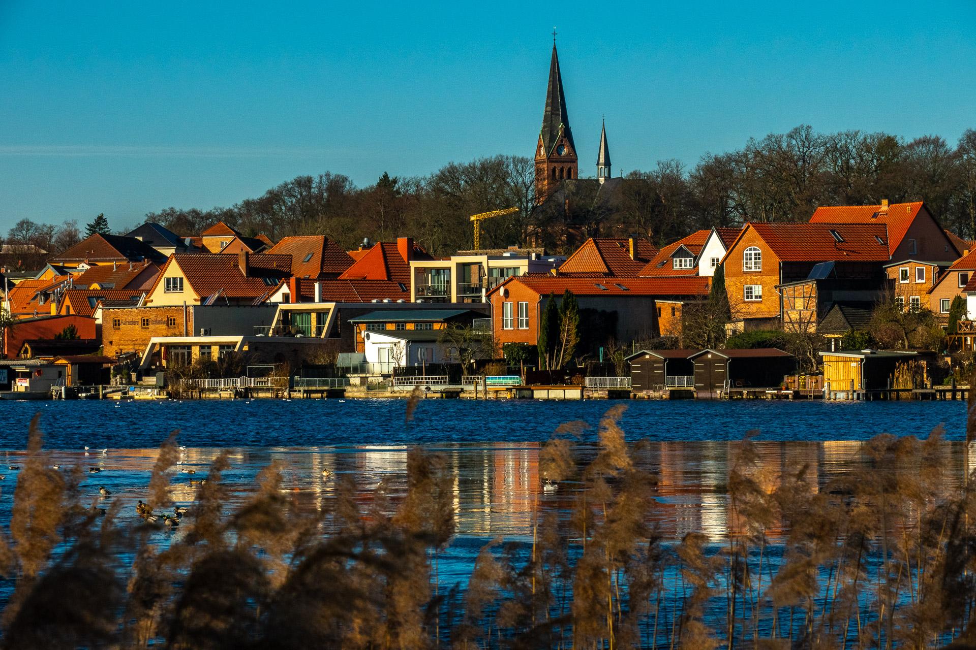 Malchower Kirche, davor der dünn mit Eis bedeckte See, Fassaden leuchten in der Sonne