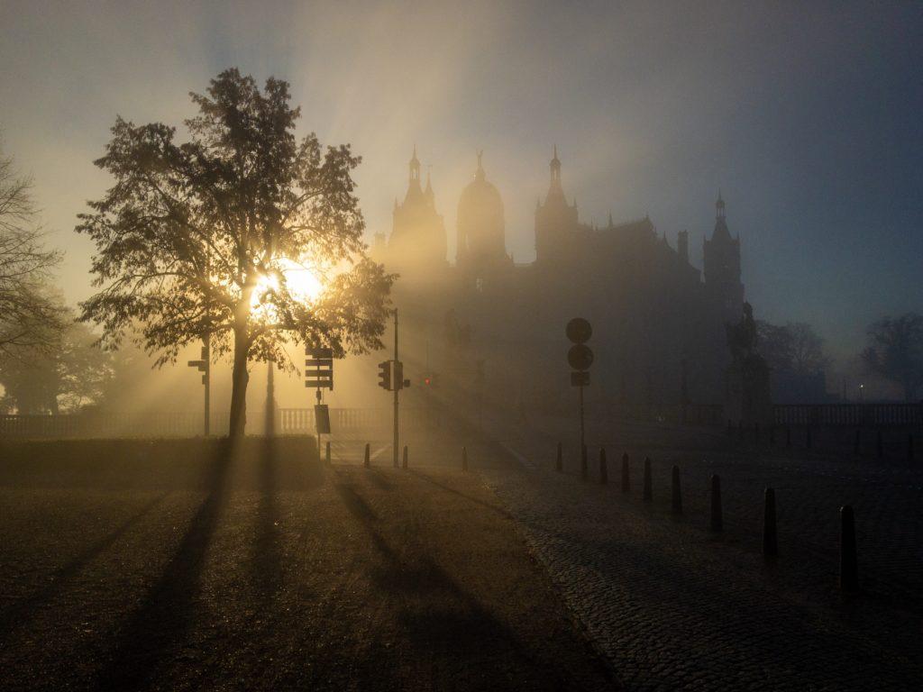 """Morgensonne leuchtet durch Nebel und Dunst am Schweriner Schloss. Es bilden sich goldene """"Strahlen"""" im Dunst."""