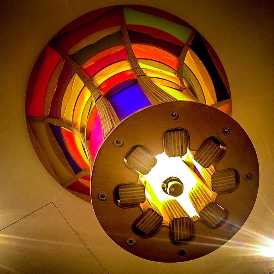 Bunte Deckenlampe mit vielen bunten Rechtecken um einem runden Holzgestell