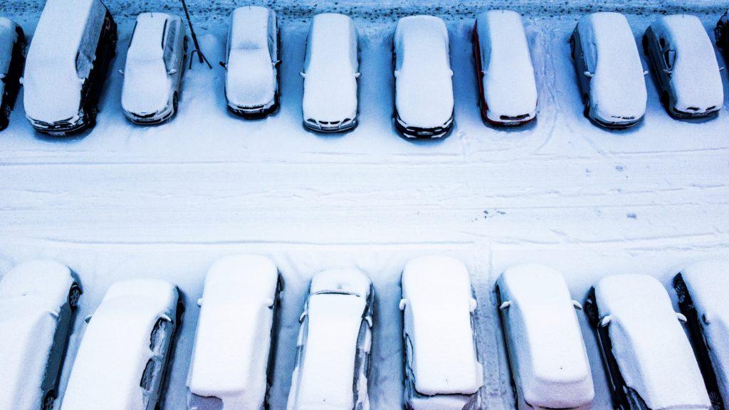 Schneebedeckte Autos parken auf beiden Straßenseiten, von oben gesehen.